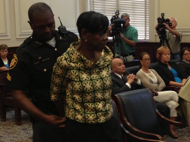 Melowese Richardson is led away in handcuffs.