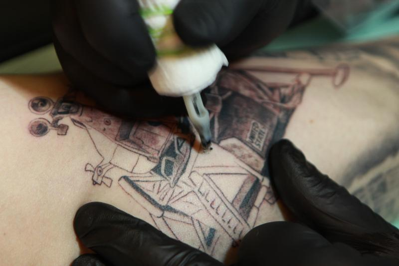 Artist Troy Coe working on a tattoo