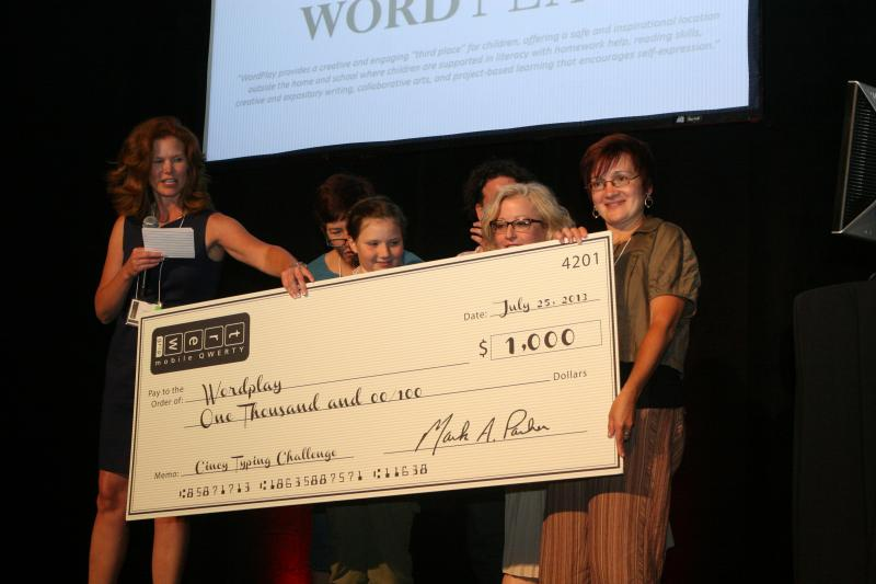 Ann Parker, vice president of Outlier Technologies, presents the proceeds of the celebrity online typing challenge to WordPlay representatives.