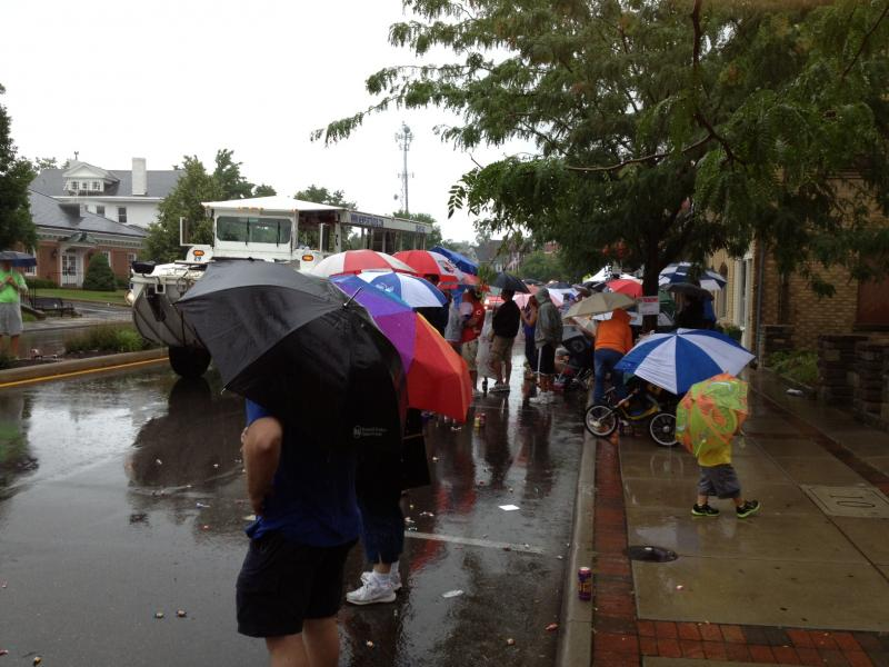 Parade watchers try to stay dry under umbrellas