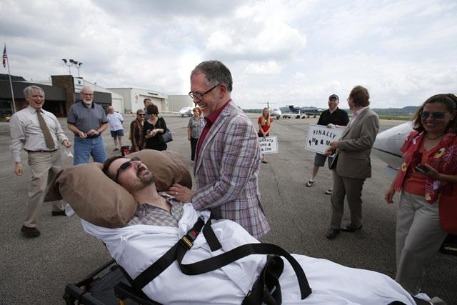 John Arthur (on the stretcher) and Jim Obergefell get married on a Maryland tarmac in July.