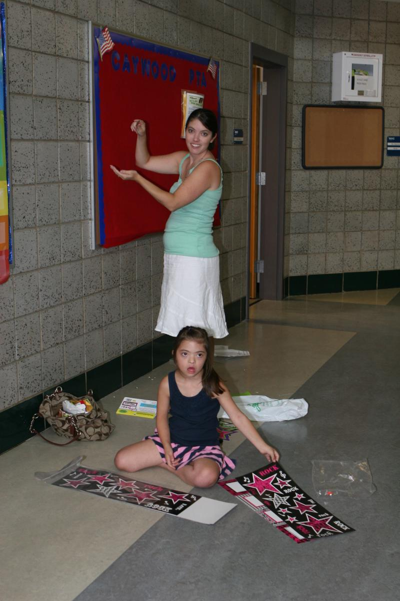 Caywood Elementary PTA president Mandy Jamison and 8-year-old daughter Clara, of Crestview Hills, ready the PTA bulletin board for the new school year.