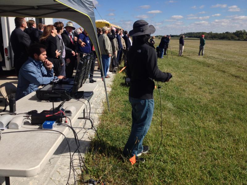 People line up to watch the test flight, remotely controlled from the tent.