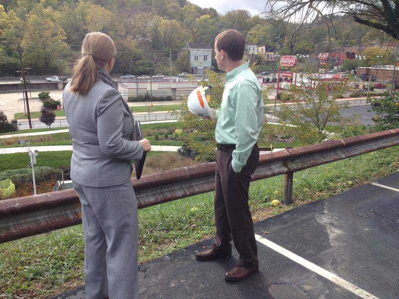 from left: MaryLynn Lodor and Andrew Reynolds look down on an area where a new urban waterway will flow to prevent flooding and sewage backup.