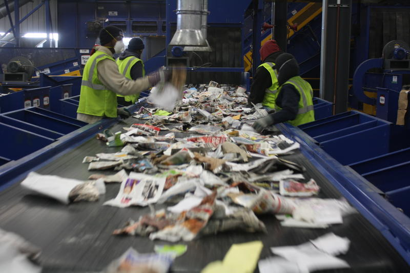 Employees work to ensure only paper is left on this conveyor belt.