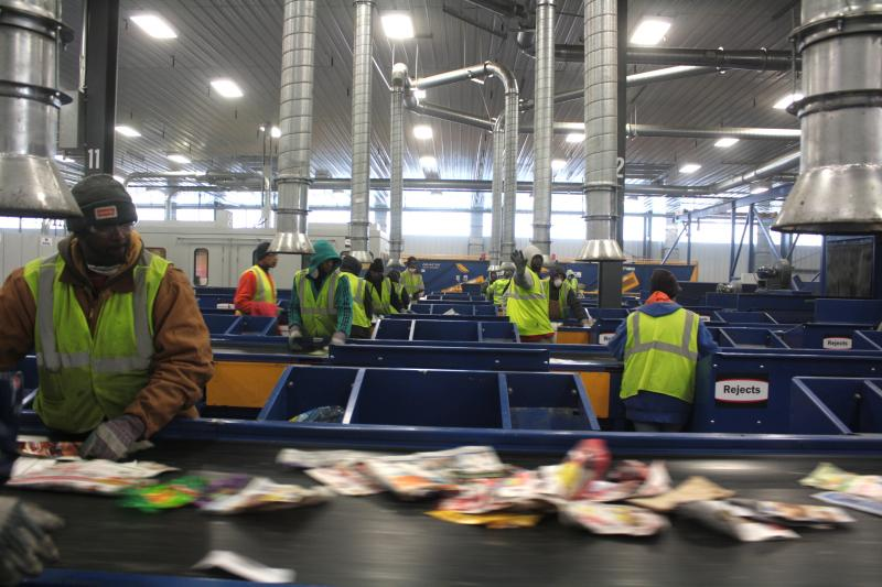 Workers sort plastics from metal and paper.
