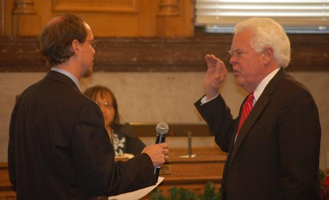 Council member David Mann taking his oath with his son.