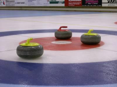 Curling stones, 44 pounds of smoothed granite, gliding across the ice.