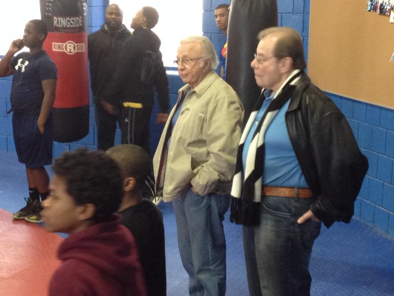 Buddy LaRosa (light brown jacket) and Art Neuman (black jacket) watch from the sidelines.