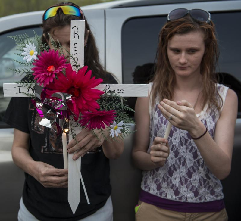 Friends hold a cross and candles during a roadside vigil for Samantha Ramsey who died after she was shot by a Boone County, KY Sheriff's deupty while allegedly trying to run him down.