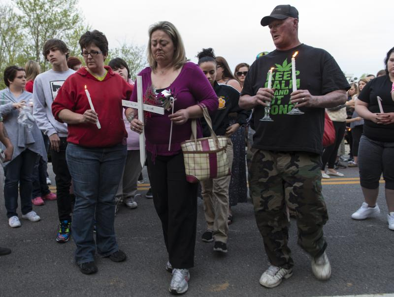 Brandi Stewart carries a cross to the scene where her daughter, Samantha Ramsey, was shot.
