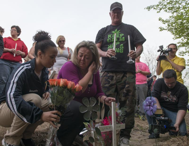 Brandi Stewart, center, is joined by friends at a roadside vigil for her daughter, Samantha Ramsey.  Ramsey was shot by a Boone County, KY Sheriff's deputy and later died.