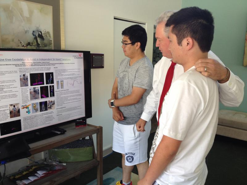 Garvin Yu, Dr. Dan Humpert and Xiangyu Zhang look at a discription of the passive exoskeleton device.