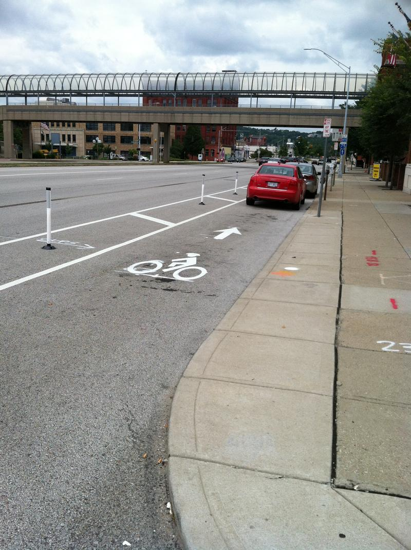Two cars parked in the new protected bicycle lane on Central Parkway near Music Hall.