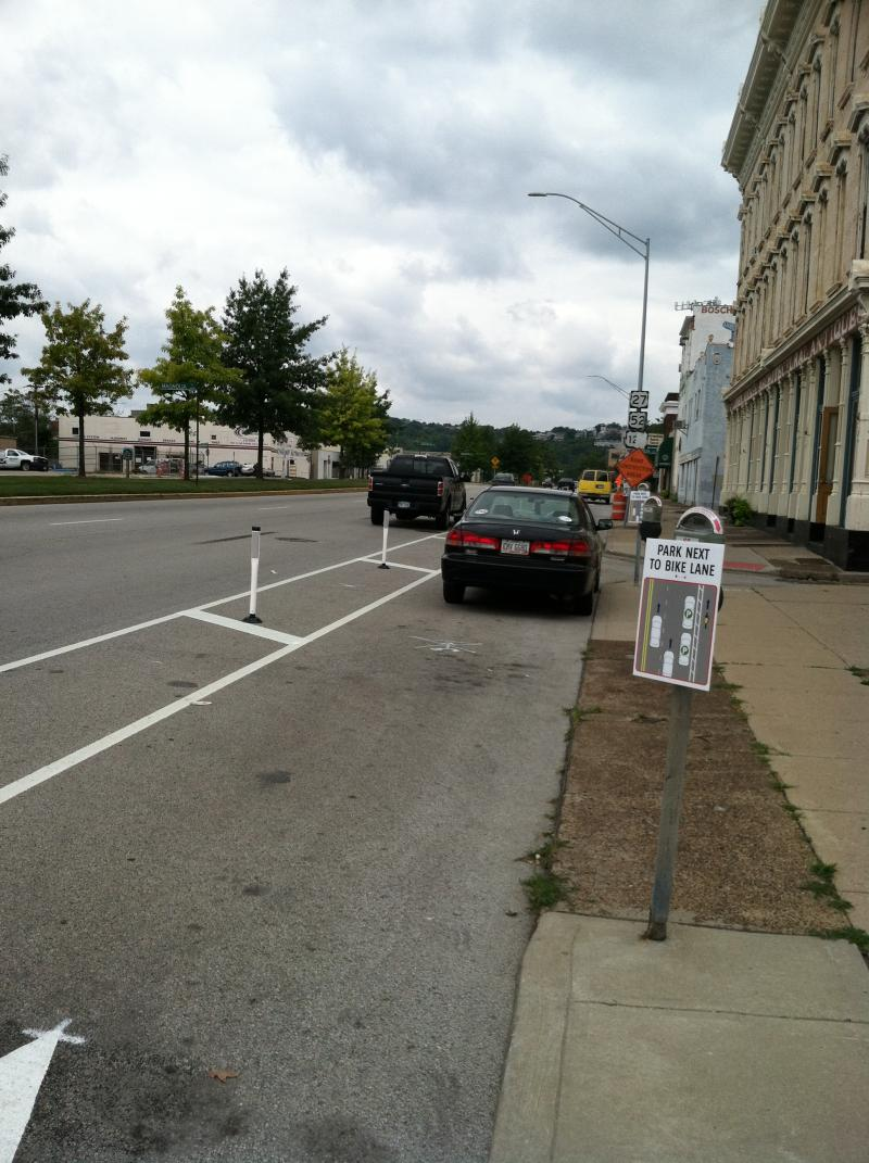 Two vehicles parked on Central Parkway with new bicycle lane near Music Hall.  The truck is parked correctly, the car is not.