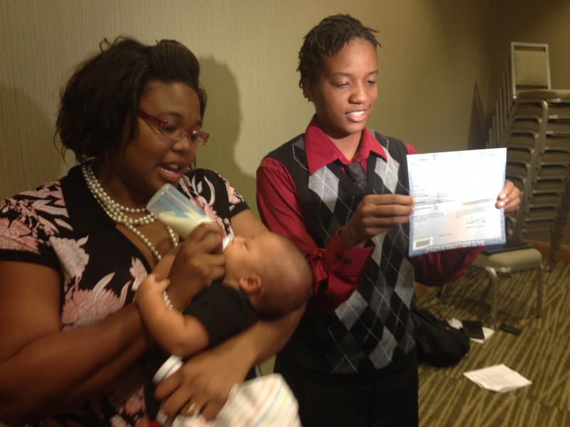 (from left) Brittani Henry Rogers holds her new baby while her wife, Brittni Rogers shows off the birth certificate with both same sex parents names on it.