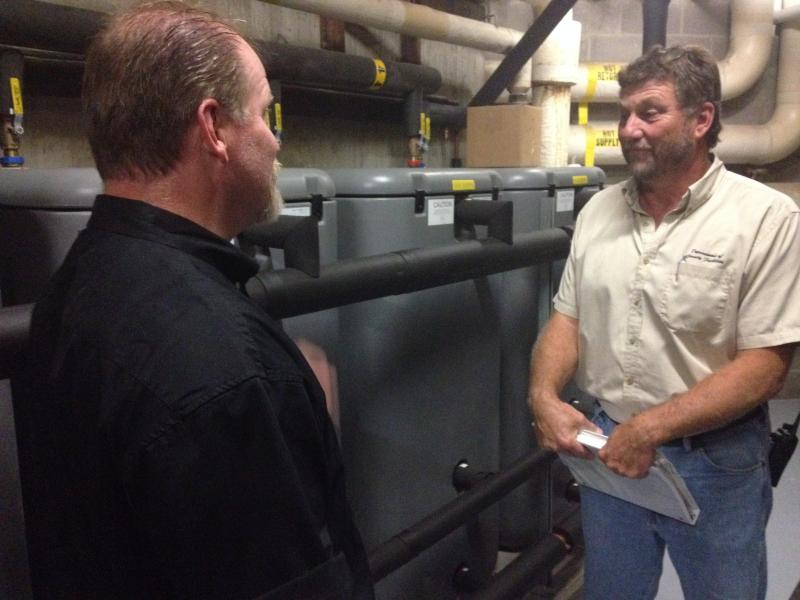 (from left) in the Justice Center room with the storage tanks are Assistant Facilities Director Tony Matre and Senior Building Manager Joe Merkt.