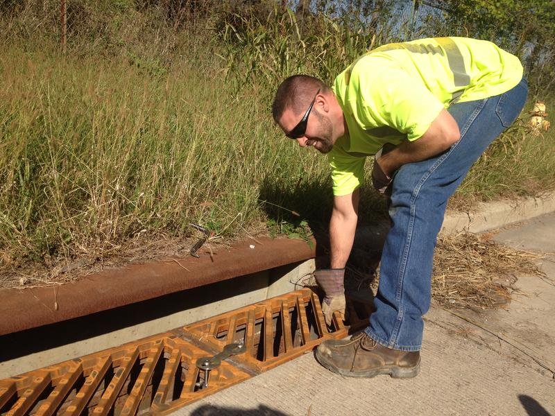 City of Cincinnati employee Chris Hines installs a lock on a replacement storm sewer grate.