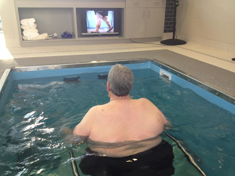 Oupatient Jim Walsh can view his progress on a video monitor while he walks on an underwater treadmill.