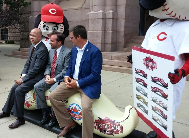 Harry Black, John Cranley and Phil Castellini demonstrate the statues are meant as benches.