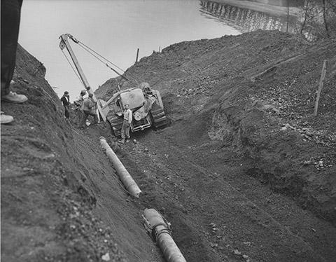 Workers dug a trench in the bottom of the river to install the old pipeline in 1947.