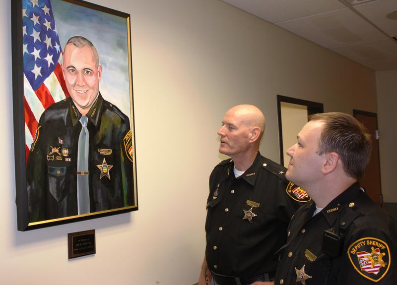 Deputy Lipps shows Sheriff Neil the painting of Deputy Nicholas (Nick) Hoevel which hangs on the wall of Patrol District 3 in Sycamore / Symmes Townships.