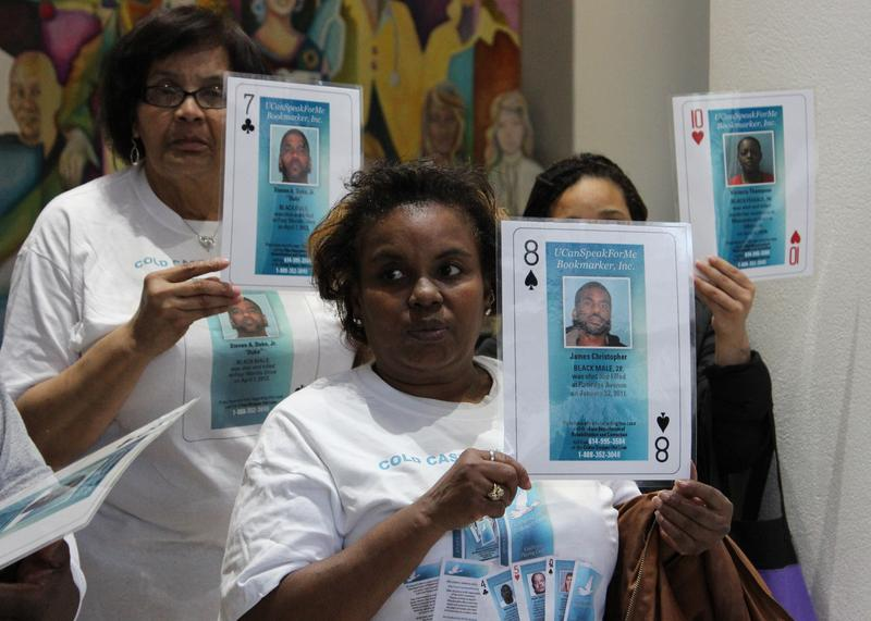 Family members hold up copies of the playing cards representing their loved ones. Decks will be sold in the jail store for $3 per pack.
