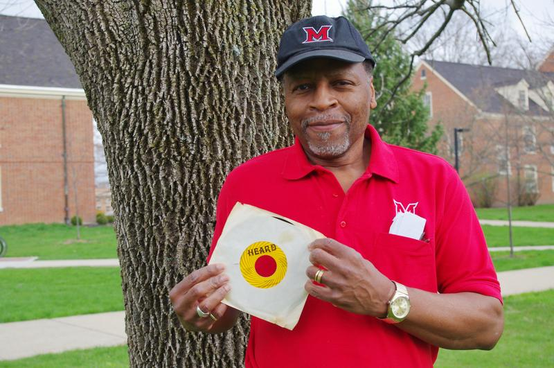 "Musician John Hurd stands on Miami University's campus, where he works, holding an original copy of the 45 rpm record ""Heard."""