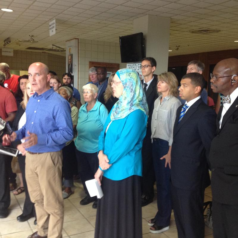 Rev. Chris Beard (at the podium) and other religious leaders call for local and national leaders to respond with love and respect in the wake of recent killings.