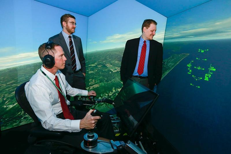 Standing at left is UC grad and Psibernetix President and CEO Nick Ernest. David Carroll, also of Psibernetix, is standing at right. Seated at the simulator controls is retired U.S. Air Force Colonel Gene Lee.