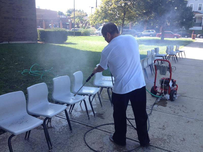 A Norwood School employee pressure washes cafeteria chairs after the flash flood.