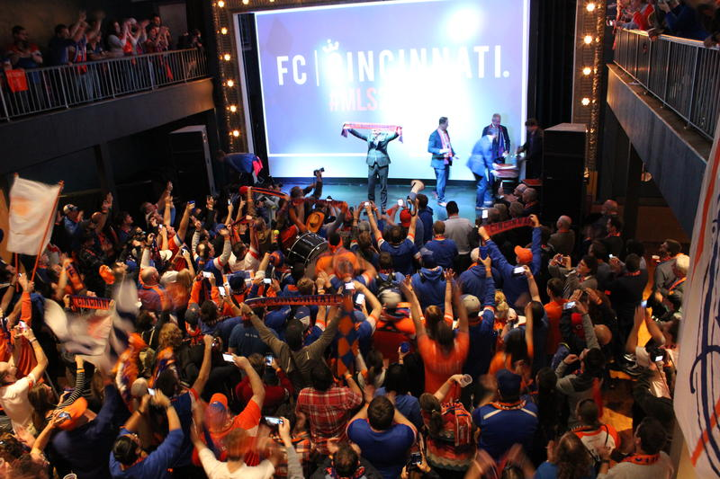 "MLS Commissioner Don Garber raises an ""MLS 2 CINCY"" scarf during a town hall about FC Cincinnati."