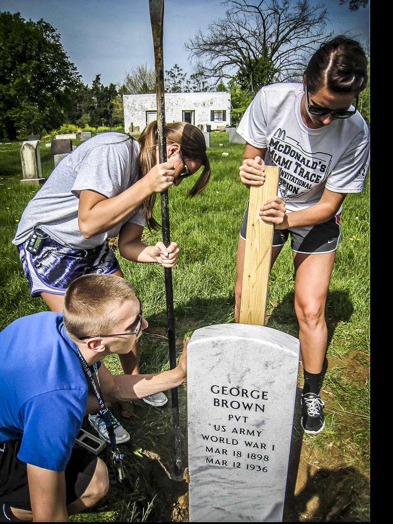 LaRue's students placing new gravestone.