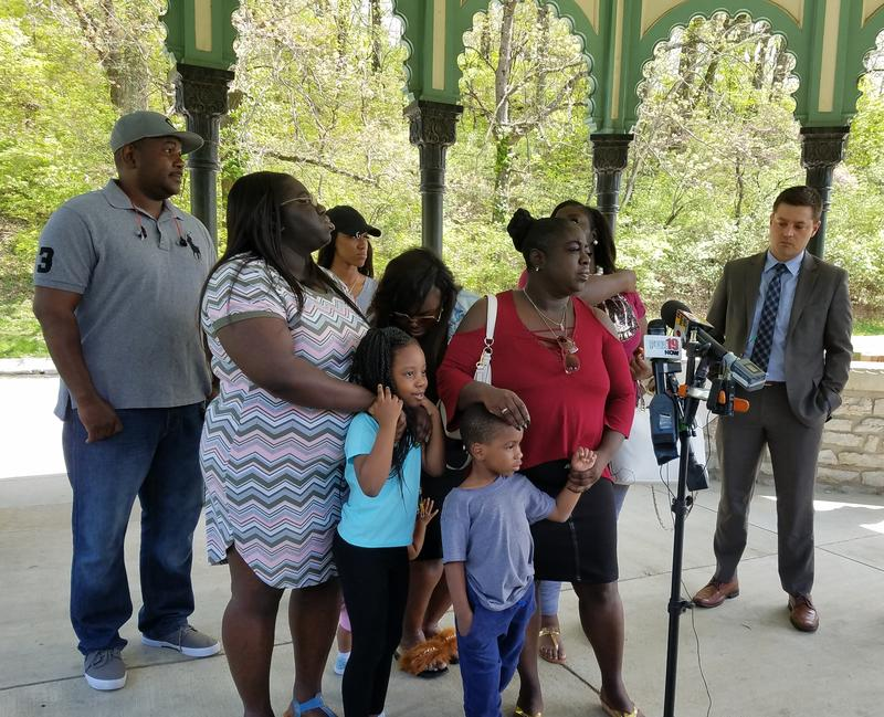 O'Bryan Spikes' mother, Raquel Mitchell (in red at center), speaks to media while surrounded by her family, including Spike's young children.