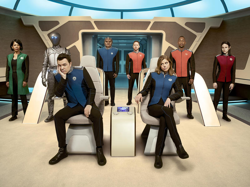 """Seth MacFarlane (seated at left) created and stars in """"The Orville,"""" a futurist Fox drama, with Adrianne Palicki (seated) and (standing from left) Penny Johnson Jerald, Mark Jackson, Peter Macon, Scott Grimes, J. Lee and Halston Sage."""