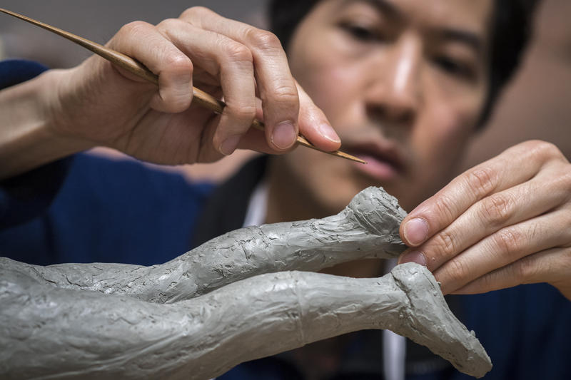 Sculptor Tom Tsuchiya makes an adjustment to the cleats on a clay model.  Nearly 80 percent of the work he does on the project goes into work on the clay model.