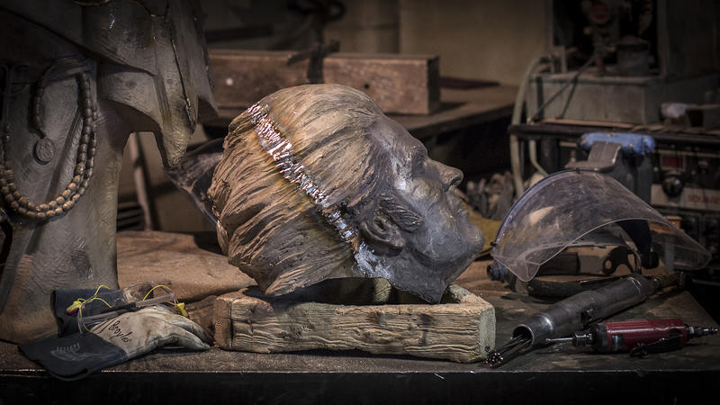 The head for the statue is positioned on a workbench and ready for welding to the body.