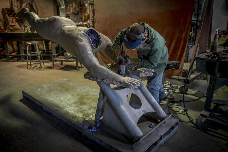 Sean Neal, chief artisan, grinds the statue during the finishing process before welding the head into place.
