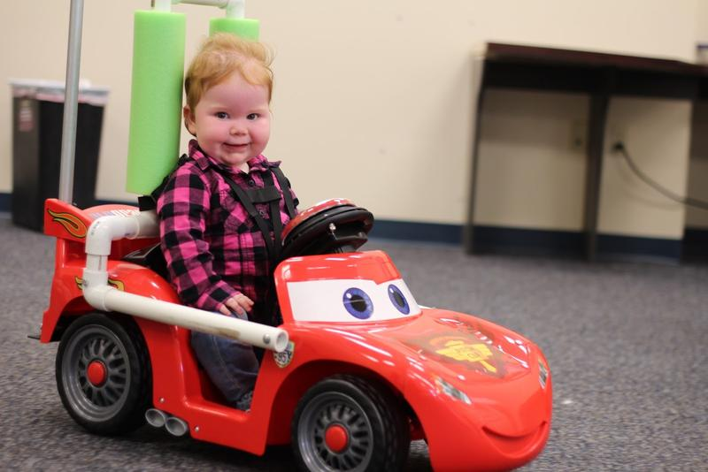 Volunteers retrofit these motorized toy cars with hand controls and headrests.