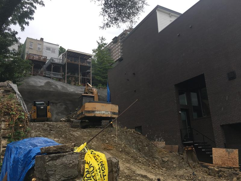 The townhouse to the left is one of two damaged when a retaining wall made up of huge concrete blocks came crashing down in May. Construction crews almost have the hill stabilized.