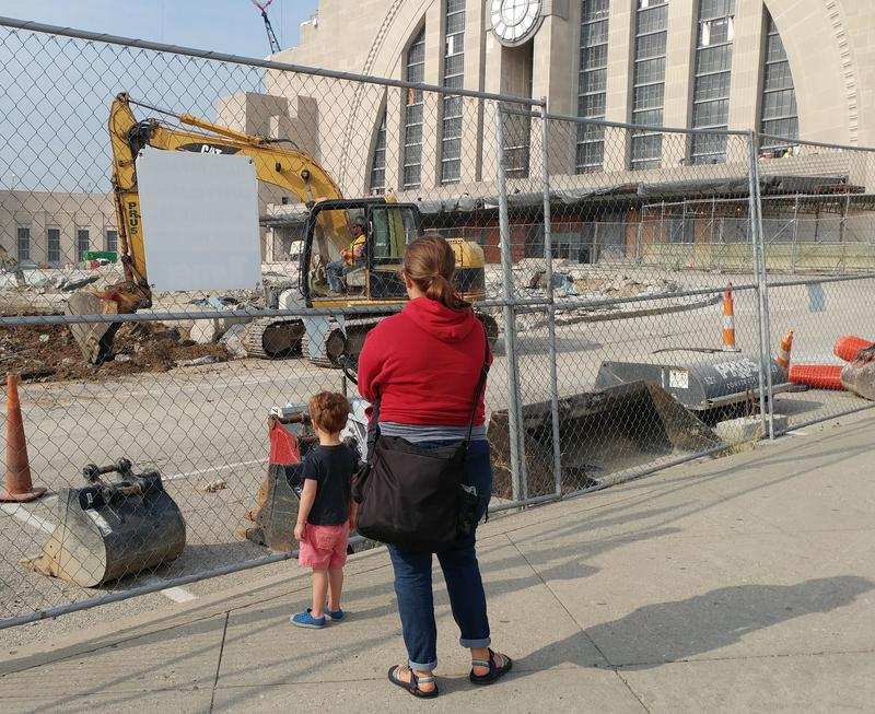 A young boy and his mother watch exterior construction outside Union Terminal.