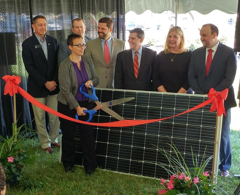 L'Oréal and solar company officials cut the ribbon in front of a solar panel.