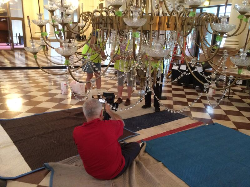 Videographer Louie Bourgeois films as removal of the Music Hall lobby chandelier on May 29, 2016.