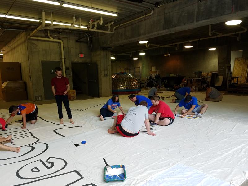 More than a dozen members of the American Outlaws, Die Innenstadt and The Pride work on Tuesday night's tifo.