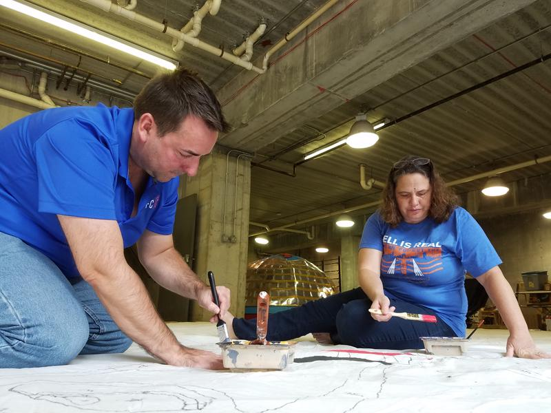 Bill Wolf and Joan Gish took up paint brushes Sunday evening to help create a tifo for Tuesday's game.