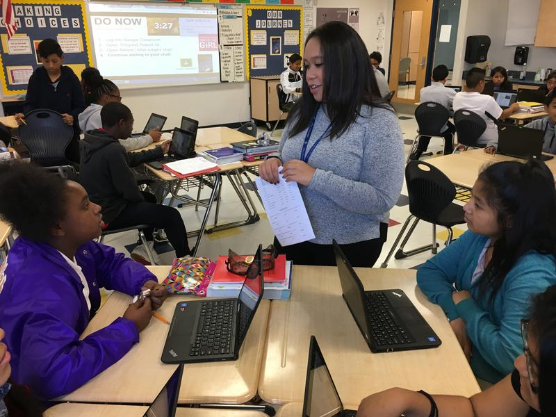 Roberts Academy teacher Tiana Gilbert interacts with students during her 8th grade English class.
