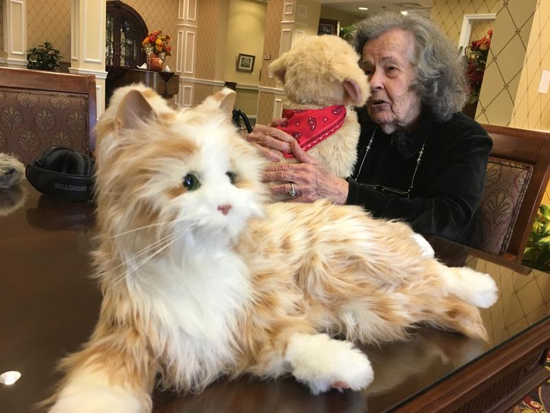 Resident Jean Koch cuddles a robotic dog while one of two cats waits for somebody to pick it up.