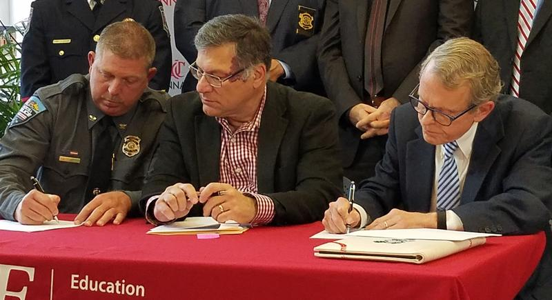From left, Madeira Police Chief David Schaefer, UC's Ed Latessa, and Ohio Attorney General Mike DeWine sign a data sharing agreement.