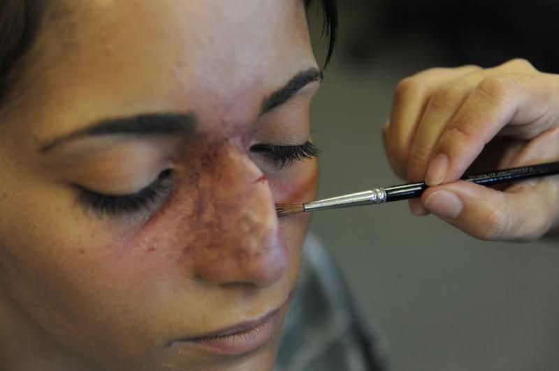 U.S. Air Force Staff Sgt. Kyla McKnight, 18th Contracting Squadron contracting administrator, has make-up applied to resemble a broken nose for the Domestic Violence Awareness campaign on Kadena Air Base, Japan, Oct. 9, 2012.