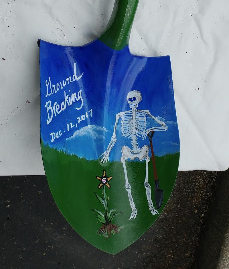 The shovel was decorated for the ceremony with crime scene tape on the handle and a painting on the blade.